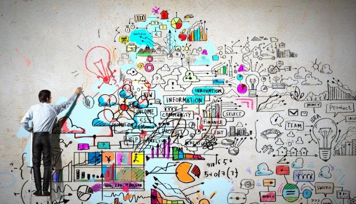 Ein Mann malt bunte Zeichen und Symbole an die Wand. Kreativ.